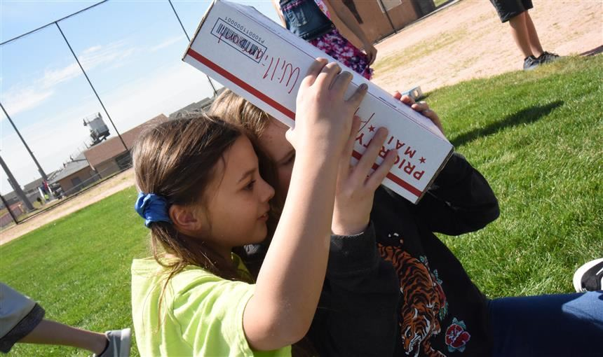 Amber Williamson, left, and Rylee Doerfler, both 11, sixth graders, view eclipse Aug. 21 at FMS.