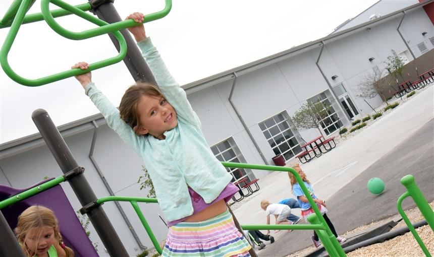 Students swing into fun on the monkey bars, a popular piece of the playground equipment, at the Fal