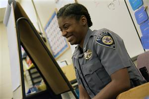 Deputy smiles and enjoys her time reading to a third grade class in District 49.