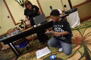 Isaiah Rhone, 13, eighth grader, takes command of a robot at College and Career Fair Sept. 15.