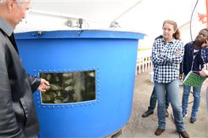 Jordan Nahabetian, a senior at SCHS, looks on as Nick Schreifels from YWAM Emerge discusses a fish holding tank.