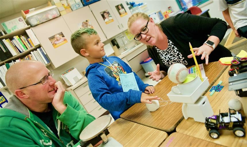 James Haag and his second-grader Bentley, listen to Teresa Howe, RES teacher, during STEM Night