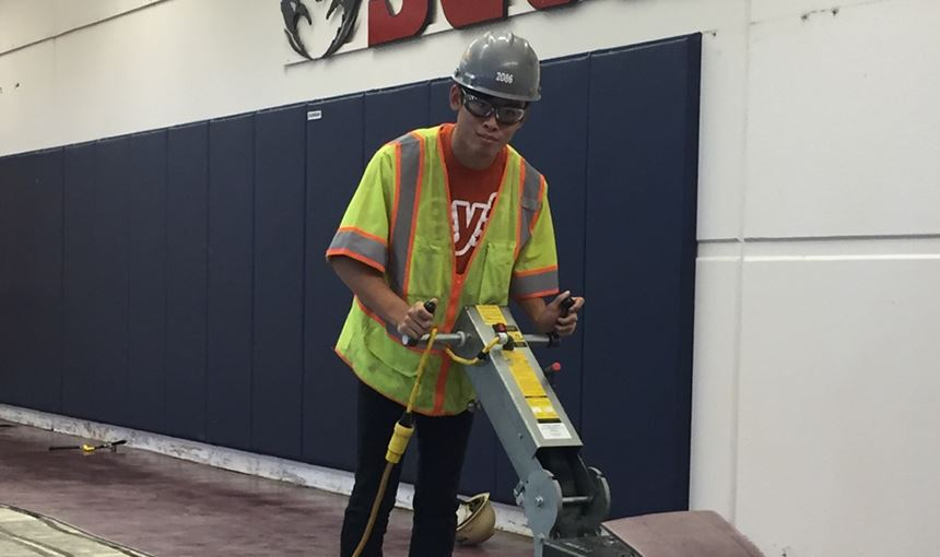 Eli Hawkins, SCHS twelfth-grader, removes flooring in the athletic wing Sept. 18.