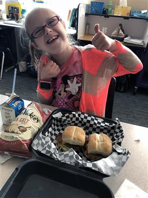"Josie Pellegrin, seventh grader, gives a ""thumbs up"" to the lunch she ordered from Marlee Ray's Food Truck Sept. 11 at SMS."