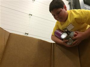 Stephen Jannicola reaches for cans during the 'Canstruction' event at Care and Share Food Bank.