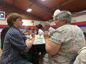 Owen Gruber, eighth grader visits with Falcon resident Lynne Eagle.