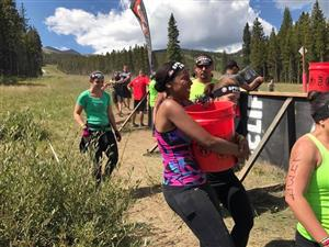 Annamaria Miller, ELD teacher at SES, carries water during the bucket brigade at Spartan Race in Breckenridge Aug. 26.
