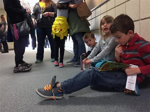 Travis Ragland, 9, SES third-grader, reads a new book in the hallway during literacy night May 18.