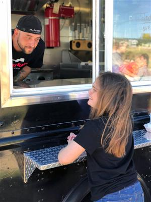 Mikaela Timmerwilke, sixth grader, orders a burger from Marlee Ray's Food Truck Sept. 11 at SMS.