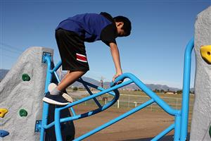Student reaches peak of jungle gym at new playground for PEAK Education Center Aug. 30.