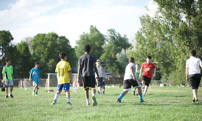 Players gather on the field behind Evans International Elementary School for Summer Soccer
