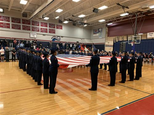 Sand Creek and Falcon cadets hold big flag before game.