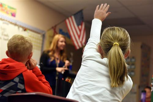 Fourth-graders raise their hands