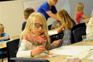: First-grader Nyah Campbell, 6, paints a flower.