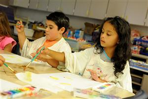First-graders Christopher Lacombe, 6, and Francesca Rodriguez, 6, paint flowers.