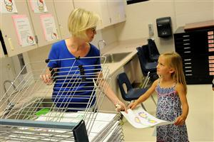 Kerri Hite, art teacher, helps first-grader Kenna Abbot, 6, place her painting in a drying rack.