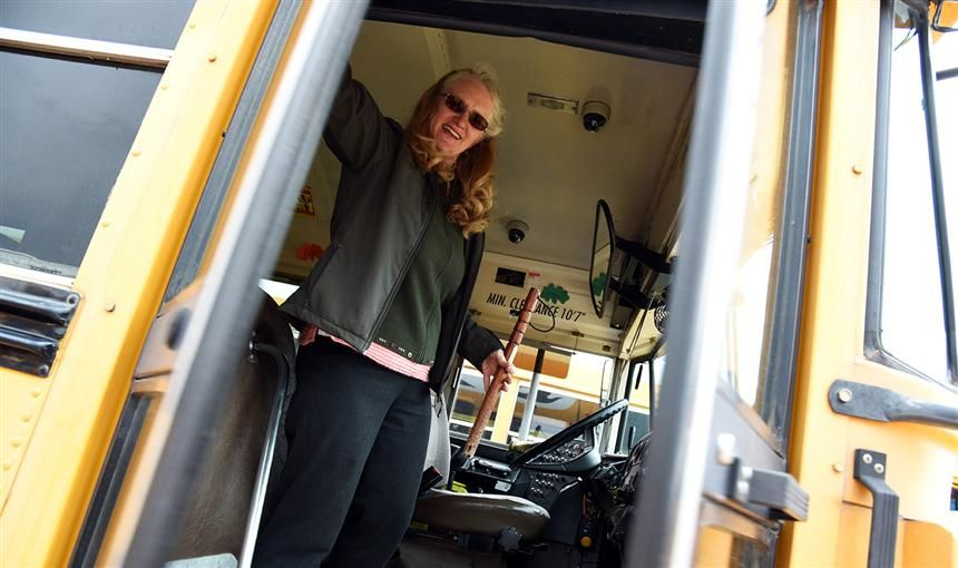 Leatha Hansz closes the door to her bus after conducting a safety check at the District 49 bus lot.
