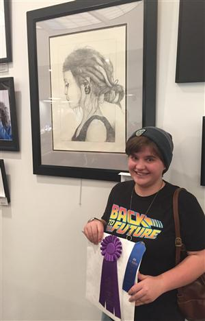 Megan Yorke stands with her piece at the District 49 art show.